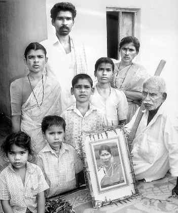 "The outdated portrait — all the family had — of Pedda Narsamma, surrounded by the eight-member household she held together. Deaths like Narsamma's are rarely counted as ""farmers' suicides."" In social perception, the `farmer' is a landed male with a patta."