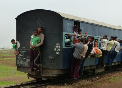 People riding on back of long distance railway train in India